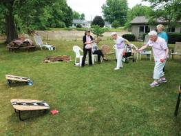 Sisters Rita Clare Gerardot and Joann Quinkert try their hand at corn hole by Saint Joseph's Lake