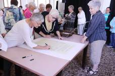 Sister Denise Wilkinson (left) and Sister Cynthia Lynge sign the Providence Climate Agreement as Sister Rosemary Nudd looks on.