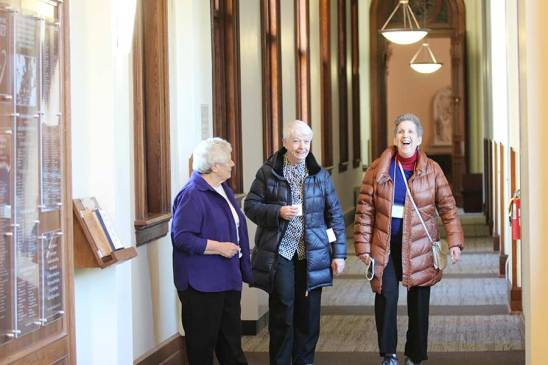 Sister Teresa Costello with Sister Shawn Marie McDermott and her Providence Associate Companion Josephine Carbonaro walk down the hall at the Providence Associate orientation as they move into their spiritual journey of the coming year.