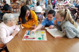 Sister Rita Clare Gerardot plays a game of Sorry! with three volunteers