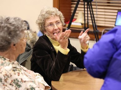 Providence Associate Jeanie Fentz speaks with sisters and associates at her table.