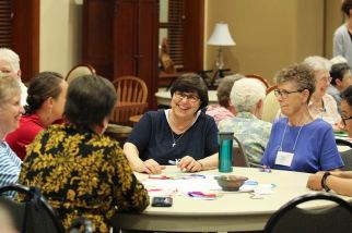 Sister Carole Kimes laughs with those at her table, including Sister Mary Tomlinson, right.
