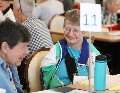 Sister Patty Wallace smiles during table discussion at annual meeting.