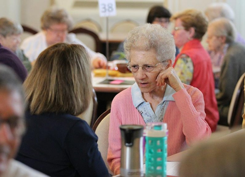 Sister Clelia Cecchetti speaks with a Providence Associate at her table on the first day of meetings.