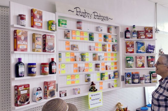 Pantry Partners wall highlights the area churches and individuals who support it, with names on various types of cans and boxes.