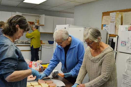 Sister Ann Casper (in blue) making sandwiches with others for a gathering at Garfield Towers in Terre Haute.