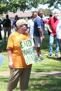Sister Beth Wright with her sign among those gathered