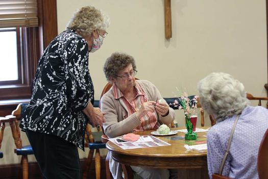 Sister Mary Mark Dede shows something to Sister Jenny Howard