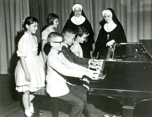 Sister Regina Marie McIntyre (right) with Sister Rose Dolores Thuis (RIP) instructing students on playing the piano at St. Charles Borromeo School in Bloomington, Indiana.