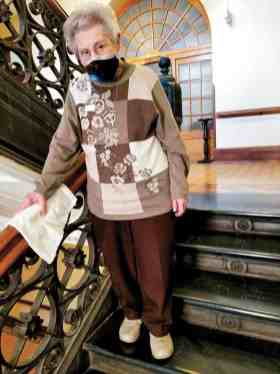 Sister Mary Lois Hennel wipes down the railings on the Providence Hall stairs to help ward off a COVID-19 outbreak.