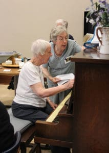 Two sisters in front of a piano.