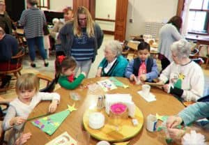 Older sisters working on a craft with preschoolers.