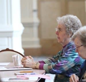 Sister Gloria sits at a table praying