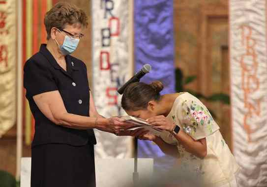 Sister Jessica kisses the Bible held by Sister Dawn.