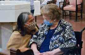 Sister Joni visits with her friend Sister Rita Ann Wade before the start of the ceremony.