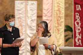 Sister Joni wipes a tear during her profession of vows.