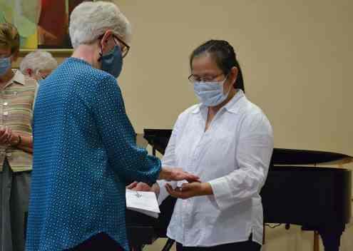 Sister Marsha Speth, director of postulants, blesses Lelie's hands
