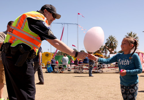 Police officer sharing SpunLight organic cotton candy with girl