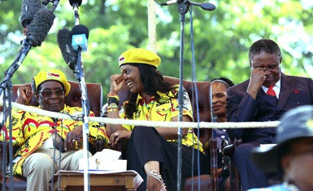 Президент Зимбабве Роберт Мугабе со своей женой Грейс и вице-президентом Фелекезела Мпоко (справа) на митинге солидарности в Хараре