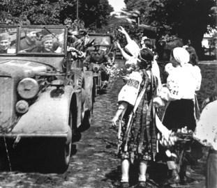 Jóvenes ucranianas vestidas de traje típico, arrojan flores sobre un convoy de soldados de la Wehrmacht. Ucrania, Julio de 1941.