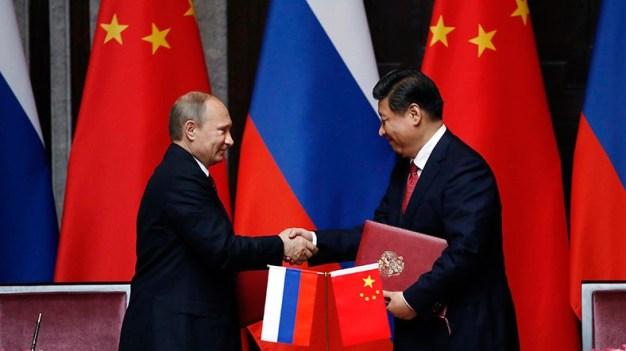 20 de mayo 2014, Shanghái. El presidente de China, Xi Jinping (Der) y el presidente ruso Vladimir Putin, firman una declaración conjunta destinada a ampliar la cooperación en todos los campos y coordinación de los esfuerzos diplomáticos para cimentar las relaciones de China-Rusia, una asociación estratégica integral de cooperación se ha consolidado después de las conversaciones en Shanghai. Foto: © AFP/Scanpix.