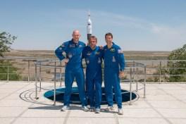 Cerca de las dependencias del Hotel del Cosmonauta, la Expedición 40/41 formada por Ingeniero de Vuelo Alexander Gerst de la Agencia Espacial Europea (izquierda), el comandante de la Soyuz Maxim Suraev de la Agencia Espacial Federal Rusa, Roscosmos, (centro) y el ingeniero de vuelo de la NASA Reid Wiseman posan para fotos el 21 de mayo como parte de sus ceremonias tradicionales de formación previas al lanzamiento. Crédito de la imagen: NASA / Victor Zelentsov.