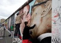 Dmitri Vrúbel (I) y su hijo Artiom (D), remueven el grafitti de la famosa pintura del beso fraternal entre Leonid Brézhnev y Erich Honecker en la Galería del Este. Varias personas y turistas limpiaron 1,3 kilómetros de sección del muro, Berlín, Alemania, 27 de abril de 2014. Foto: © Kay Nietfeld / dpa / Corbis.
