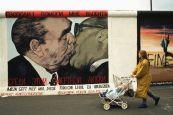 Una mujer pasa al lado del mural que representa el 'Beso entre hermanos' de Leonid Brézhnev y Erich Honecker en el muro de Berlín. Foto: © Peter Turnley / Corbis / 26.09.1990 /