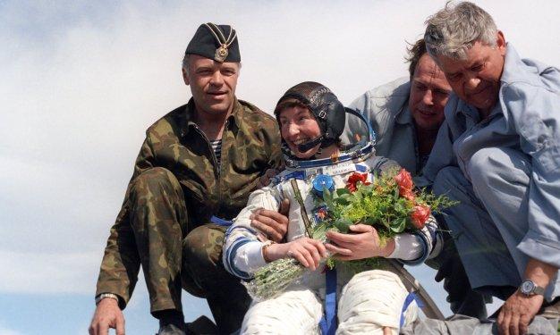 26 de Mayo de 1991: La astronauta británica Helen Sharman en su traje espacial Sokol siendo ayudada por el personal de Baikonur, con un ramo de flores después del aterrizaje de la Soyuz TM-11. El aterrizaje tuvo lugar cerca de Zhezkazgan, Kazajstán, en la Unión Soviética. Foto: © ITAR-TASS.