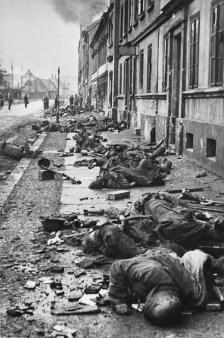 Cuerpos de soldados alemanes caídos durante los combates mano a mano contra el Ejército Rojo, al fondo los soldados soviéticos del 1er Frente Ucraniano, inspeccionan la escena. Foto: © Dmitri Baltermants.