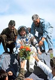26 de Mayo de 1991: Regreso de la astronauta británica Helen Sharman quien sale del módulo de descenso en su traje espacial Sokol siendo ayudada por el personal de Baikonur y recibiendo un ramo de flores después del aterrizaje de la Soyuz TM-11. El aterrizaje tuvo lugar el , cerca de Zhezkazgan, Kazajstán, en la Unión Soviética. Foto: © Science Photo Library.