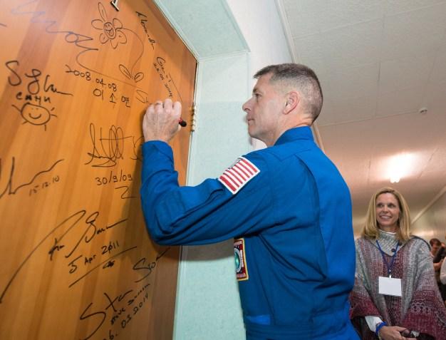 19 de Octubre de 2016: El segundo ingeniero de vuelo, el astronauta Shane Kimbrough de la NASA, firma la puerta de su habitación en el Hotel del Cosmonauta como parte de las tradiciones previas al lanzamiento. Crédito de la imagen: NASA / Joel Kowsky.