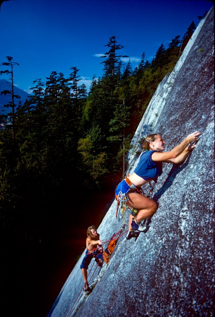 Tami Knight leads Exasperator 5.10c, with partner Peter Croft, at the base of the Grand Wall, Squamish Chief, British Columbia, Aug 1979