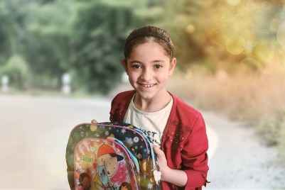 Little girl going back to school with bag.
