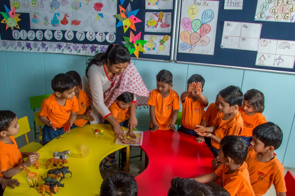 Play-based learning delivered by a female teacher, to a classroom full of early learners