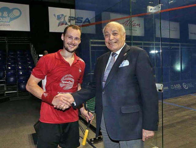Reigning champion Gregory Gaultier is greeted by British Open sponsor  Assem Allam