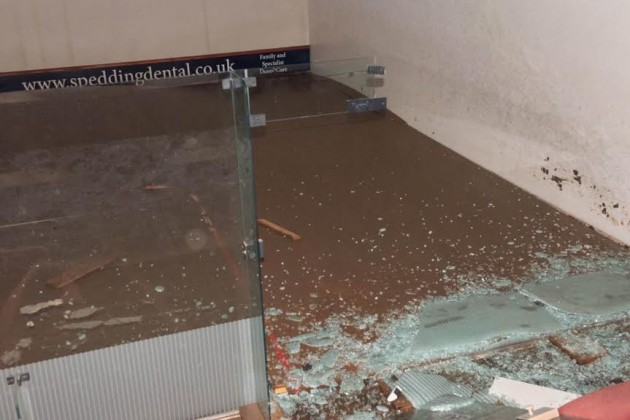 Shattered glass lies on the buckled court floor