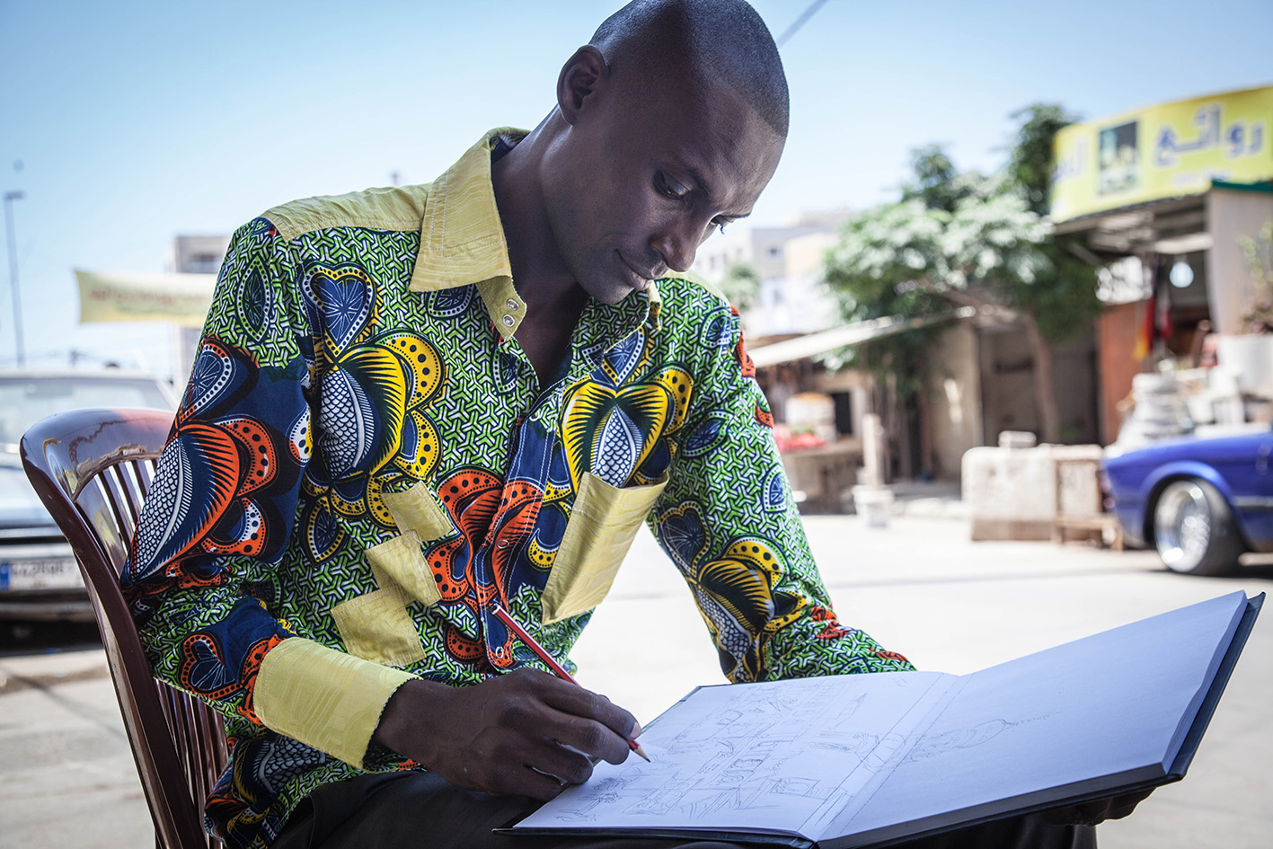 Didier Kassai draws in his sketch pad