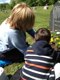 Mother and son planting flowers at the cemetery - family tradition yellow marigolds