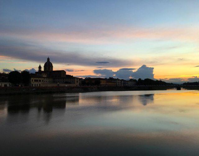 Un paradiso per chi vuole fotografare a Firenze: la vista di Oltrarno al tramonto riflessa nell'Arno sorprende e ispira sempre