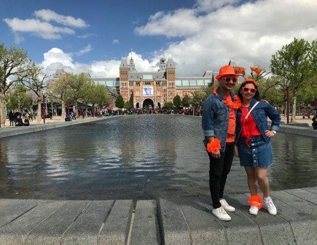 Coppia vestita d'arancio per il King's Day si fa una foto davanti al Rijksmuseum a Amsterdam