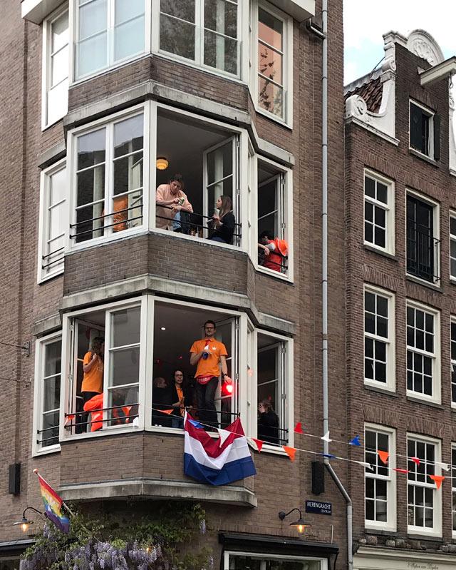 Durante il King's Day a Amsterdam molti festeggiano in casa, ballando sulle finestre spalancate