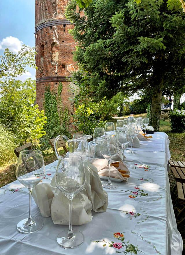 Tavolo apparecchiato all'aperto sotto la torre di Montaldo Roero