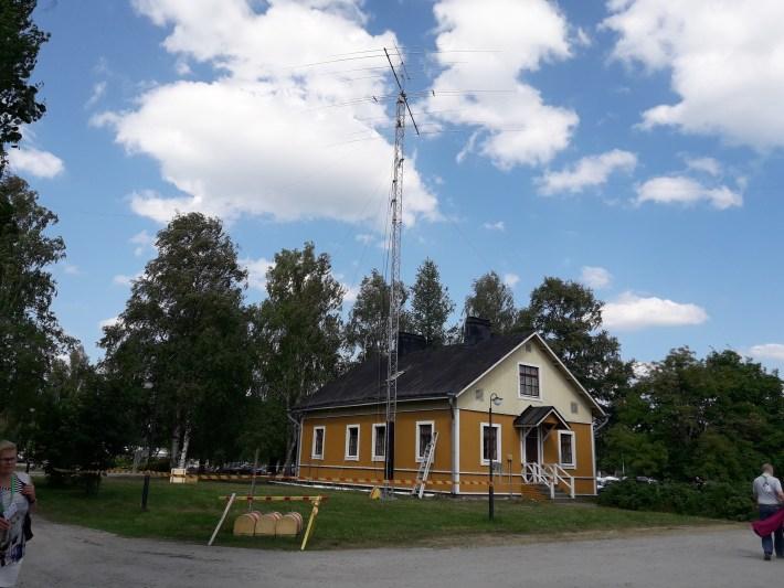 Keltavalkoinen puurakennus, masto ja antennit.