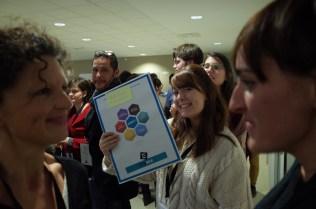 Pendant la constitution des équipes, une jeune femme montre son panneau bingo complété