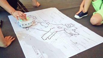Un petit robot blanc dessine un chien sur un plan de ville