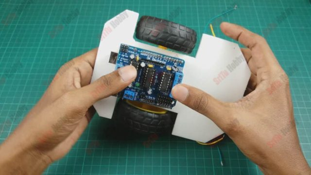 Now, attach the motor drive shield to the Arduino UNO board. Then, glue this to the car chassis.