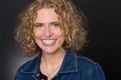 Headshot of Smiling Blonde woman in jean jacket.