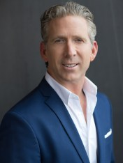 Man in blue blazer with pocket square in headshot