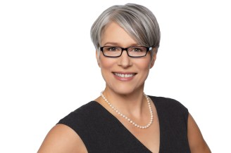Headshot of woman with natural grey hair, glasses and pearl necklace